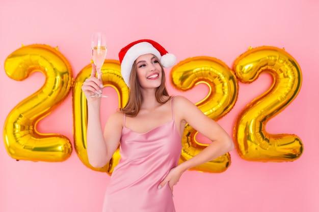 A menina sorridente do papai noel levanta uma taça de champanhe com números dourados e balões de ar no conceito de ano novo