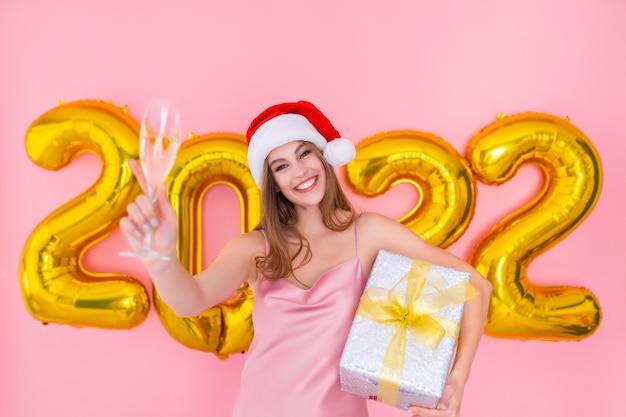 A menina sorridente do papai noel levanta uma taça de champanhe enquanto segura uma caixa de presente com balões de ar de ano novo