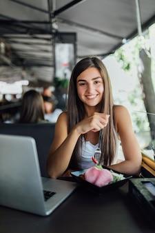 A menina sorridente está sentada no café e faz a lição de casa no laptop durante o dia