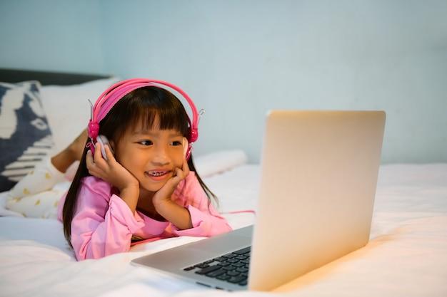 A menina sorriu feliz e deitou-se ouvindo são bao do laptop no colchão.