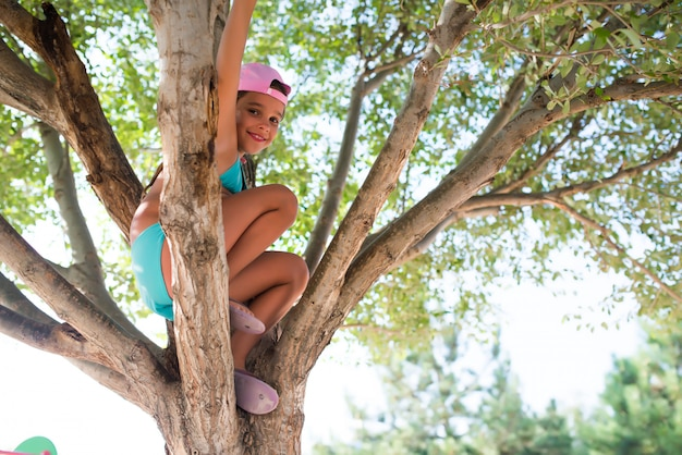 A menina subiu em uma árvore