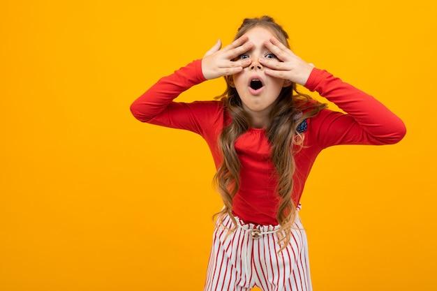 A menina surpreendida com cabelo encaracolado em uma blusa vermelha e nas calças listradas perscruta através das palmas onn laranja com espaço da cópia