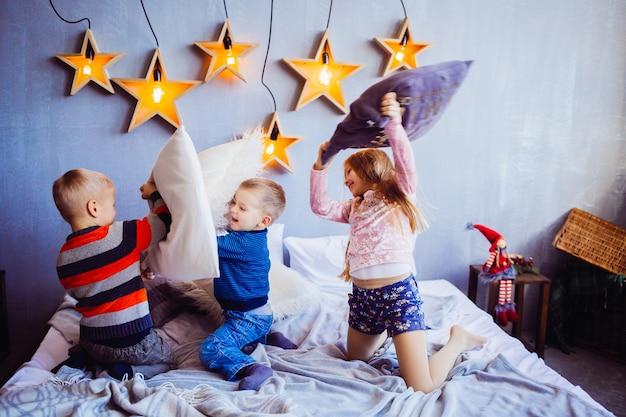 A menina sweety e meninos brincando e pulando na cama