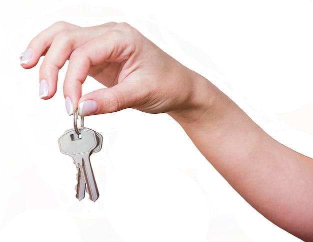 A menina tem as chaves na mão em um fundo branco e isolado