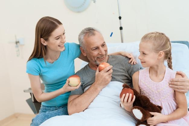 A menina tem brinquedo nas mãos com o avô doente.