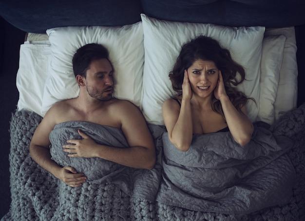 A menina tem dificuldade para dormir devido ao ronco do namorado. conceito de desconforto e insônia