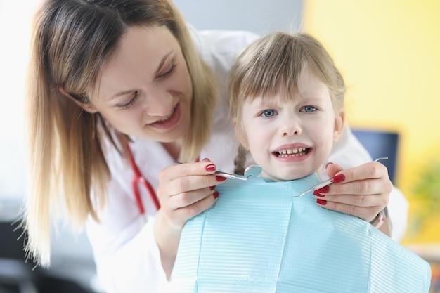A menina tem medo dos medos dos filhos do médico dentista durante o conceito de tratamento odontológico