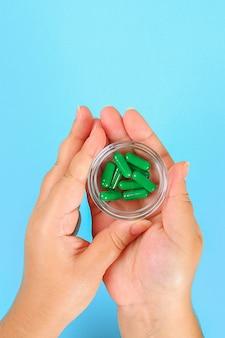 A menina tem nas mãos bolhas de vários comprimidos e pílulas sobre a mesa azul