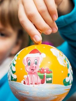 A menina tem nas mãos um brinquedo de natal com a foto de um porco