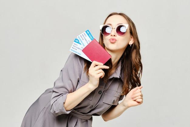 A menina tem um passaporte com um bilhete na mão e mostra um beijo.