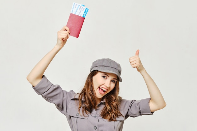 A menina tem um passaporte com um bilhete na mão e mostra um polegar para cima.