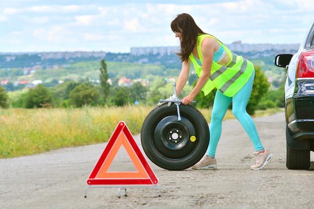 A menina tem um problema com a substituição da roda sobressalente