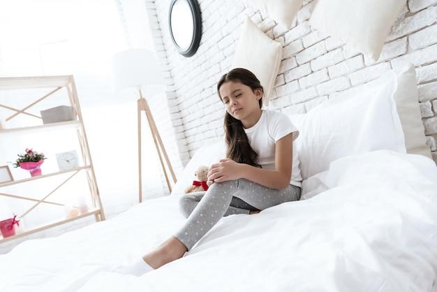 A menina tem uma dor no joelho, ela está fazendo uma massagem em casa.