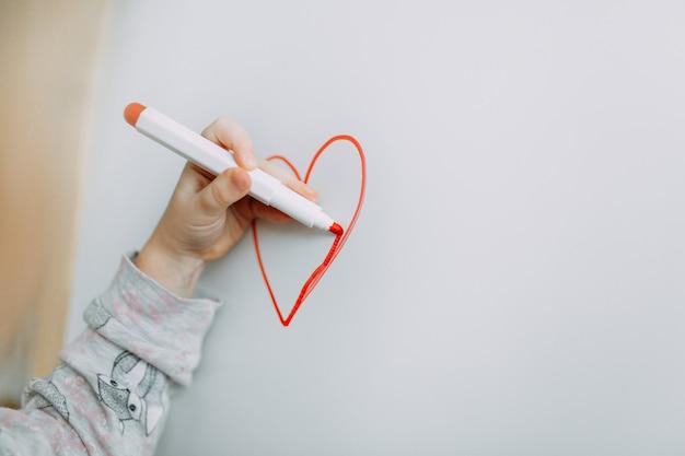 A menina tira o coração com marcador em um quadro-negro branco. dia das mães. dia dos namorados