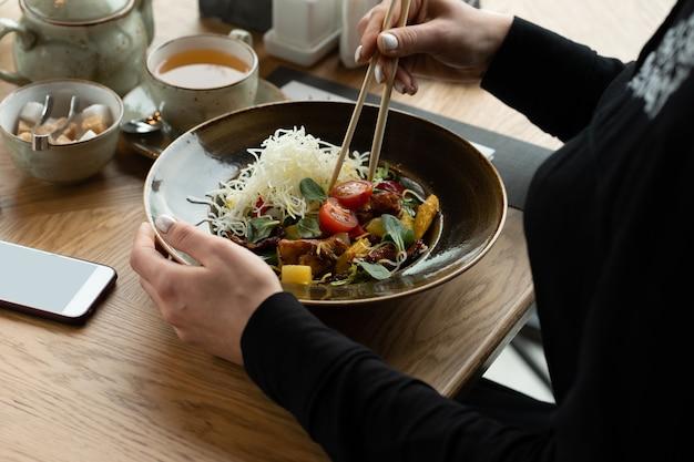 A menina tira um tomate cereja de uma salada de legumes com pauzinhos de frango, cenoura, milho grelhado e queijo. almoço em restaurante asiático. profundidade de campo rasa, fundo desfocado.