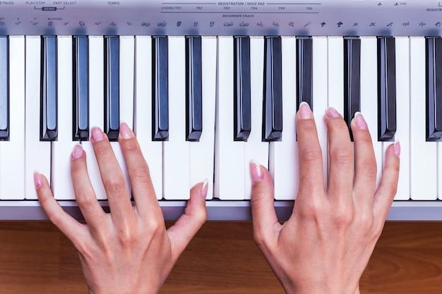 A menina toca piano. mãos de uma mulher com manicure requintado nas teclas de piano, vista superior