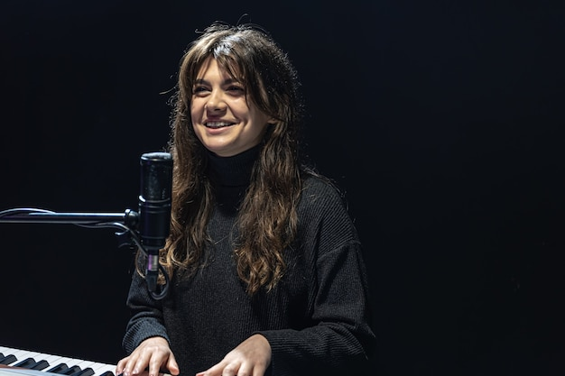 A menina toca piano no estúdio de gravação de som profissional