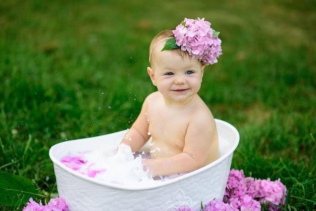 A menina toma banho em um banho de leite no parque.