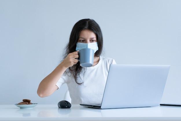 A menina trabalha em casa durante a quarentena. pandemia do coronavírus. uma garota com uma máscara cirúrgica trabalha no laptop e bebe café. trabalho distante