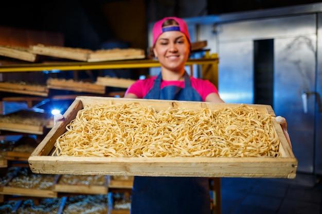 A menina trabalha na produção de espaguete. fazendo macarrão. fábrica de massas. fase de produção de massas alimentícias. macarrão cru. trabalhador com uma caixa de macarrão.
