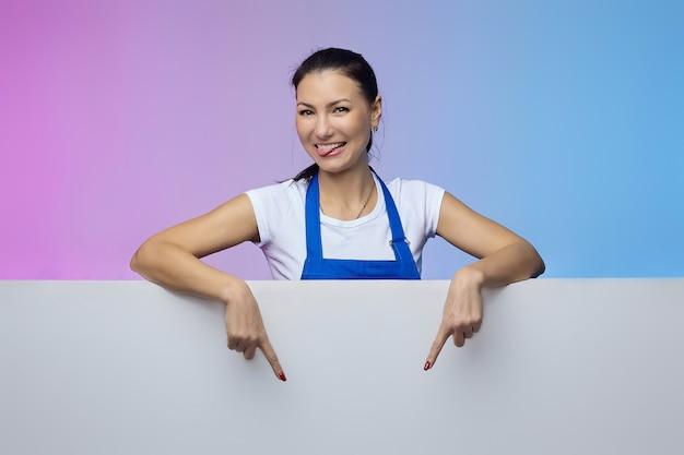 A menina trabalhadora com um avental azul de aparência asiática posa com um outdoor branco. conceito de publicidade