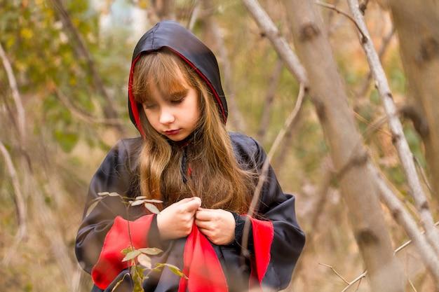 A menina triste em um manto vermelho e preto na floresta