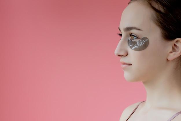 A menina usa manchas pretas sob os olhos, sorrindo, sentada em frente ao espelho. estilo de vida saudável, juventude, facial.