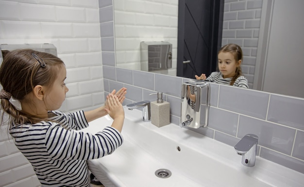 A menina usa sabonete líquido para lavar as mãos.
