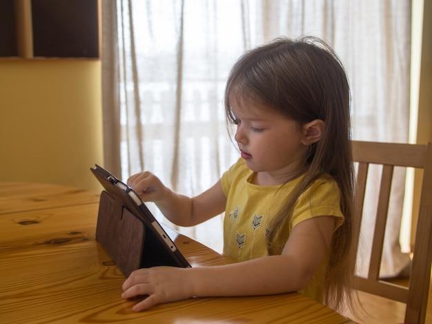 A menina usa tablet, assiste a desenhos, joga