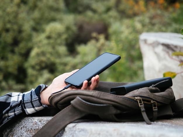 A menina usa um smartphone conectado ao banco de energia
