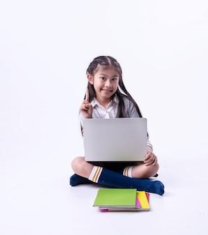 A menina usando o laptop para pesquisar dados, aponte um dedo no ar, com rosto sorridente, crianças inteligentes