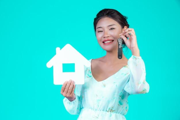 A menina usava uma camisa branca de mangas compridas com padrão floral, segurando o símbolo da casa e segurando um chaveiro com um azul.