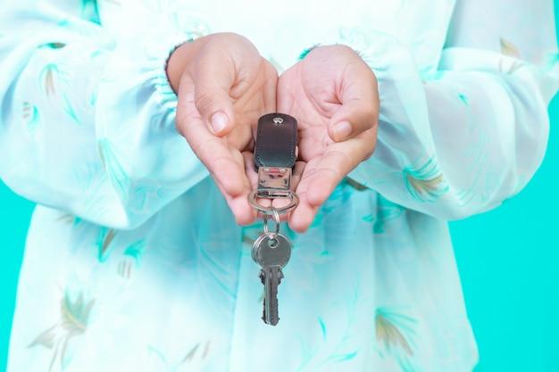 A menina usava uma camisa branca de mangas compridas com um padrão de flores segurando um chaveiro com um azul.
