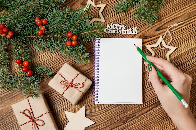 A menina vai escrever uma lista de desejos para o próximo ano contra os acessórios de natal