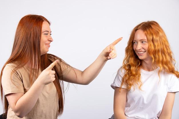 A menina, vendo algo à distância, mostra a amiga. duas meninas ruivas sentam-se em cadeiras em uma parede branca. eles fazem caretas e se divertem.