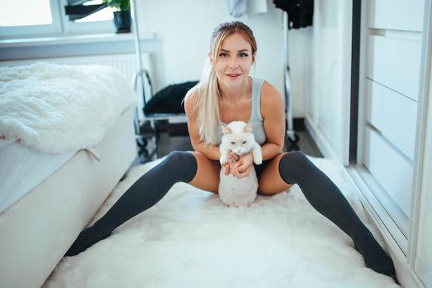 A menina veste lingerie erótica e toca a gata de forma fofa e suave sensação de jovialidade pela gata