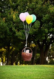 A menina voa em balões em um fundo de árvores verdes