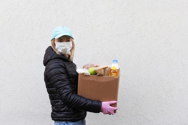 A menina voluntária em máscara protetora com caixa de comida, doação