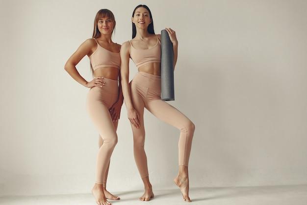 A meninas bonitas está envolvida em um estúdio de yoga