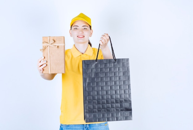 A mensageira está apresentando a caixa de presente enquanto segura a sacola com a mão esquerda em frente à parede branca