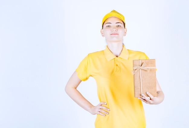 A mensageira sorridente está segurando a caixa de presente enquanto coloca a mão perto da cintura em frente à parede branca