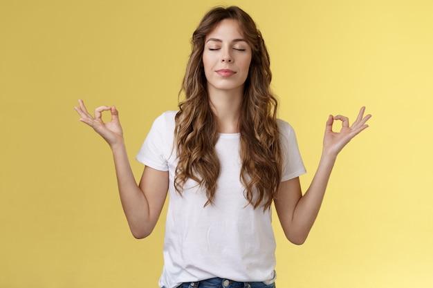 A mente vagueia pelos problemas. menina om cantando meditação feche os olhos sorrindo encantado encontrado paz relaxamento sentindo aliviado respiração prática budista mãos para os lados mudra lótus pose fazer ioga.