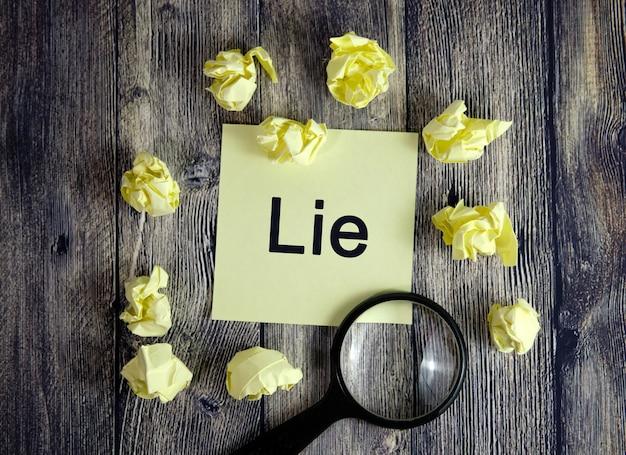 A mentira está escrita em um adesivo amarelo. seleção verdadeira, pesquise com uma lupa