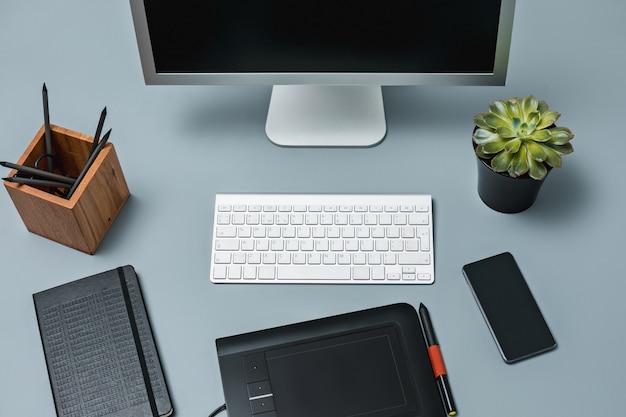 A mesa cinza com laptop, bloco de notas com uma folha em branco, vaso de flores, caneta e tablet para retoque