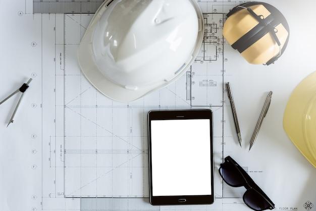 A mesa da engenharia no tempo da manhã do local de trabalho, as ferramentas de engenharia e a tabuleta com desenho de construção, vista superior de cima com trajeto de grampeamento incluíram a foto.