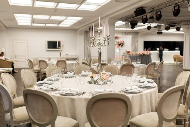 A mesa de banquete redonda branca do restaurante está decorada com flores frescas. decoração elegante para eventos