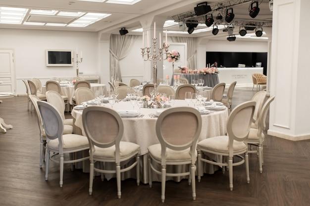 A mesa de banquete redonda branca do restaurante está decorada com flores frescas
