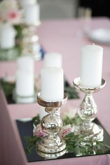 A mesa de casamento para os noivos é decorada com castiçais de prata e velas brancas.