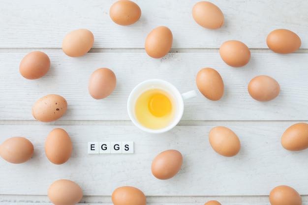 A mesa de cozinha com o ovo amarelo fresco da gema no copo branco e os ovos text a letra.
