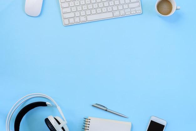 A mesa de escritório azul e equipamentos para trabalhar em vista superior e plana leigos sobre fundo azul